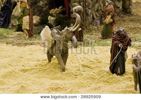 Arabic man with elephant, figurines in a crib scene.