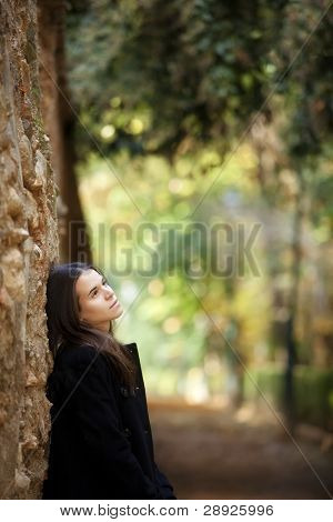 Young beautiful pensive girl in autumn background.