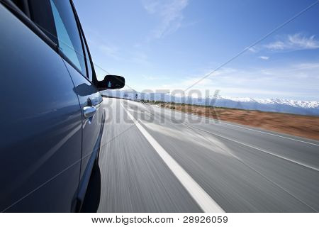 Driving at high speed under blue sky. Angled point of view