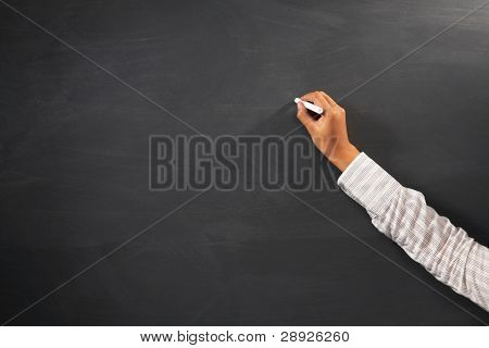 Hand of teacher holding chalk in front of blank blackboard