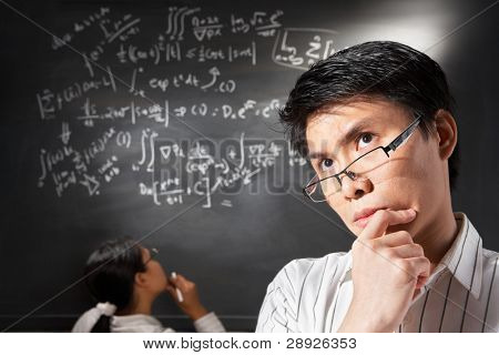 Male student pose  with female student trying to solve the equation on background