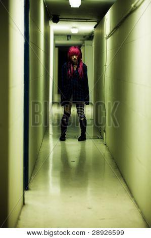 Creepy scene of a girl in dark corridor