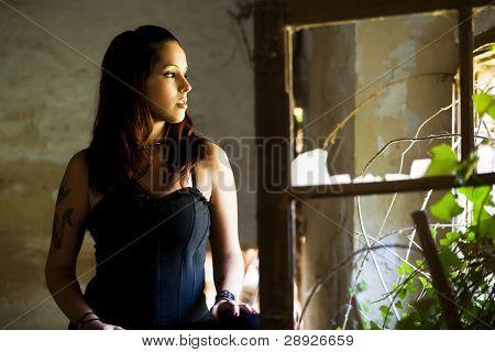Young beautiful goth girl looking at broken window.