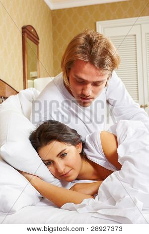 A lady ignoring her spouse on bed, a concept for couple who have conflict
