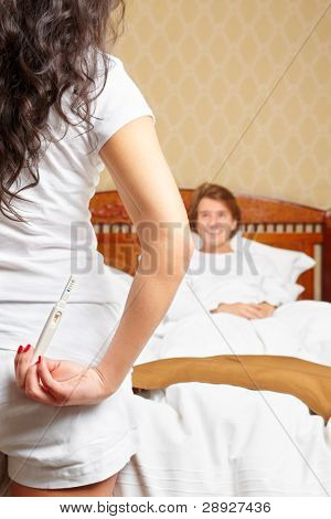 A lady is hiding her pregnancy test in front of her smiling spouse on bed