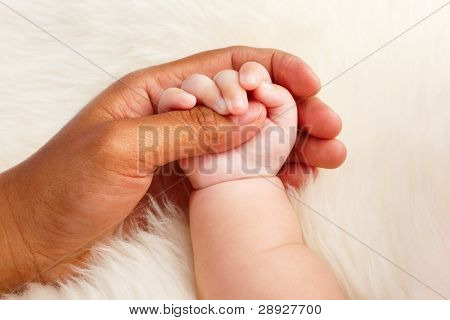 Adoption concept where dark skin parent holding hand of asian baby