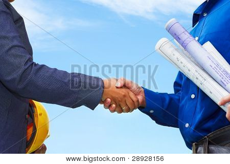 Two contractors shake hands with blue sky background