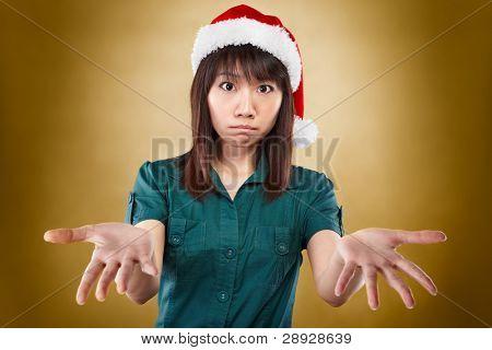asiatische Dame mit Santa Hut zum Ausdruck bringen, dass sie keine Ahnung hat