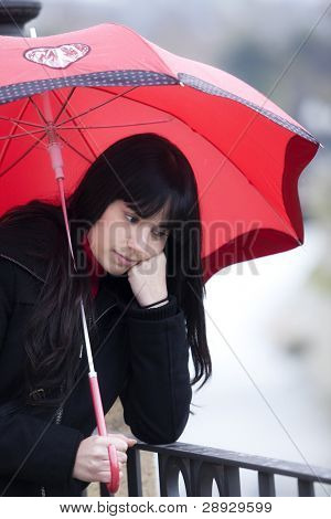 Sad girl with red umbrella with pensive gesture.