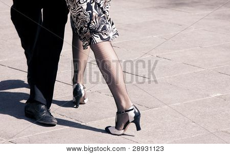 Street dancers performing tango dance. Aged warm tone.