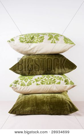 Different green pillows stacked up