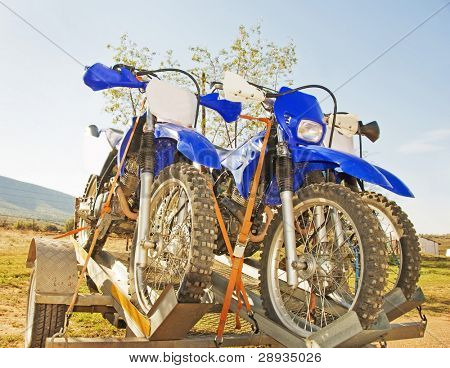 Three off road motorbikes on a trailer