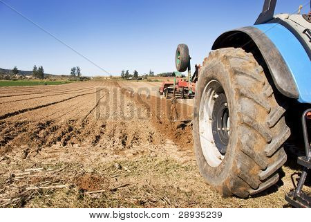 Tractor with implement cultivating a farm field