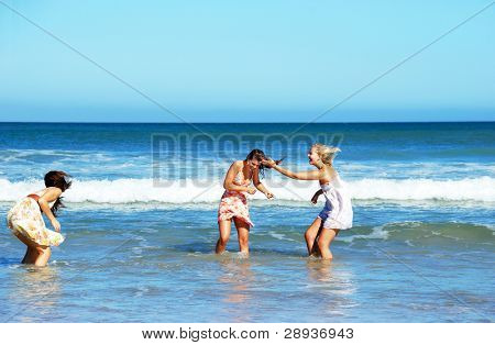 Three young woman having fun in the waves on a sunny summer day
