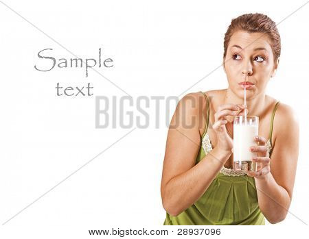 Beautiful young woman drinking a glass of milk - on a white background with space for text
