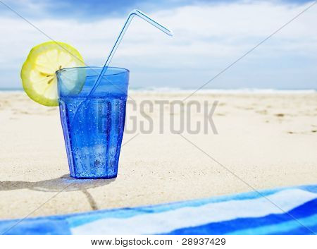 Blue glass with sparkling water and a slice of lemon and a blue beach towel on the beach