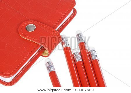 a Red notebook with red pencils on a white background - ready to study