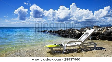 a Beach chair and diving equipment on a tropical island beach  with lovely sky and clouds - focus on the diving flippers