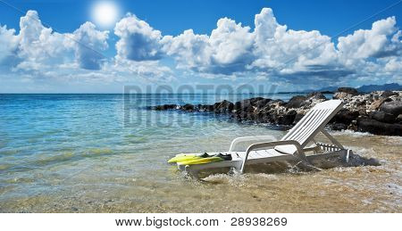 Beach chair and diving flippers on a tropical island beach