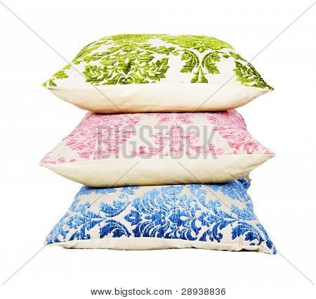 Blue, pink and green cushion stacked up on a pure white background with space for text