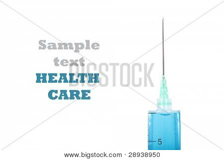 Close up of a syringe with needle filled with a blue medicine - on a pure white background with space for text