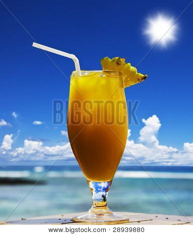 a Lovely cold fresh fruit cocktail with pineapple and straw on a tropical island beach\