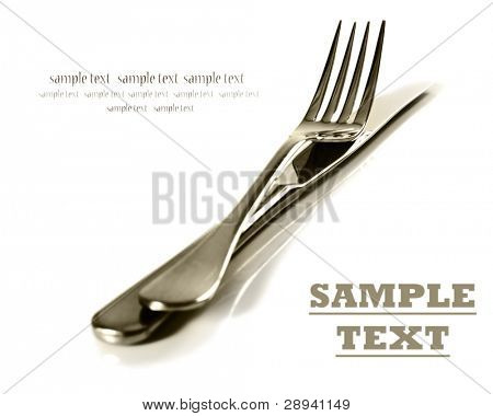 a Sepia image of a Knife and fork stacked up on a pure white background with space for text