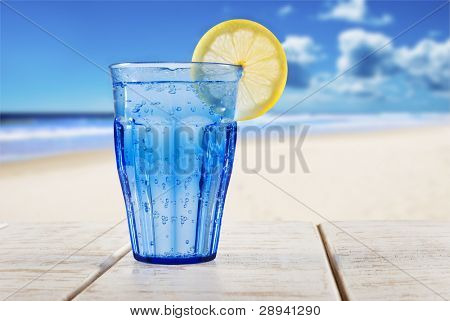 a Blue glass with sparkling water and lemon on a wooden deck overlooking a tropical beach - focus on the lemon