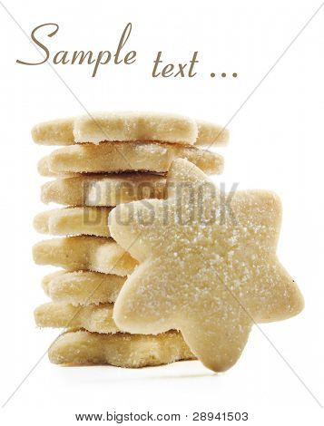 Sugar coated shortbread cookies in star shapes stacked up - on a white background with space for text