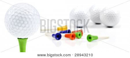 New golf balls and pins on a white background with space for text