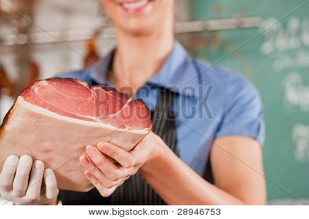 Closeup of female butcher smiling while holding raw meat