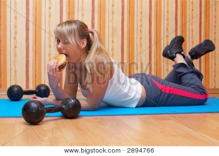 Girl Is Eating Tasty Burger After Fitness Training