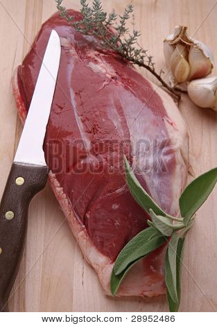 raw duck breast, herbs and knife