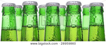 Closeup of nine green beer bottle necks over a white background. Focus is on the front two bottles and tye are covered with condensation. Extra long shot useful for a banner.
