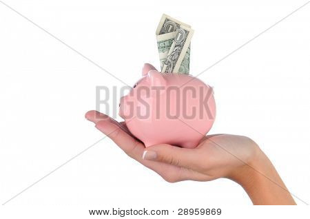 Closeup of a woman's hand holding a pink piggy bank with a dollar bill stuck in the top slot. Side View in horizontal format over a white background.