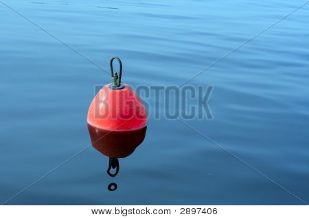 Red-Orange Buoy In The Blue Water