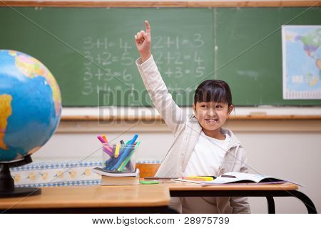 Smiling schoolgirl raising her hand to answer a question in a classroom