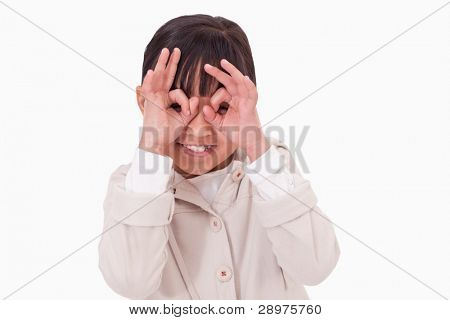 Girl putting her fingers around her eyes against a white background