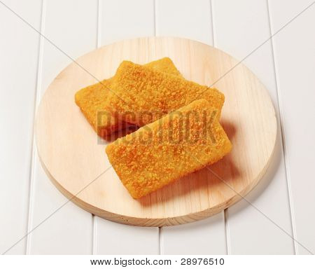 Breaded fish fillets on a cutting board