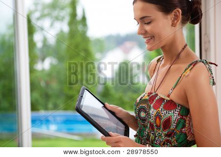 Pretty young smiling woman looking at tablet pc