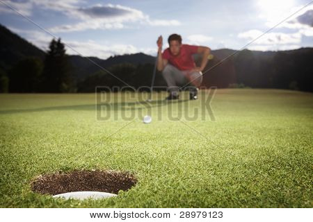 Male golf player in red shirt squatting to analyze the green for putting the golf ball into the hole.