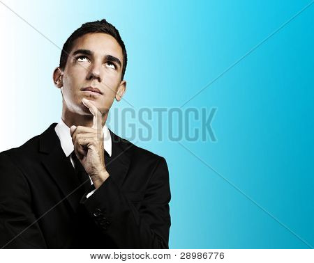 portrait of pensive young business man against a blue background