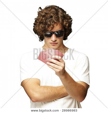 portrait of young man wearing sunglasses and playing poker over white background