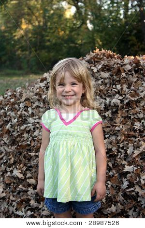 Smiling Girl in Leaf Pile