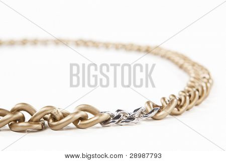 Golden chain connected with small silver chains in circular, isolated against white background. small depth of field