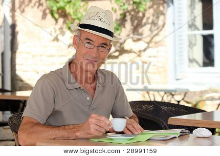 senior citizen sipping his coffee in terrace cafe