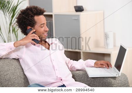 Man sat with laptop and telephone at home