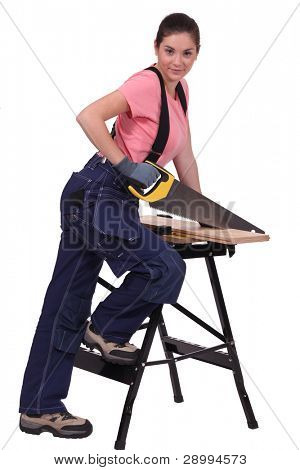 Woman sawing plank of wood