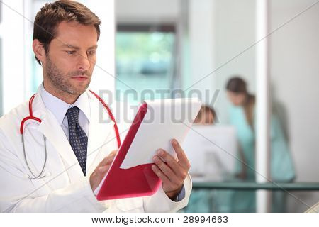 doctor in hospital reading charts