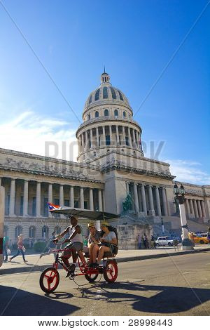 A Car-bike With Tourists Circle In Front Of The Capitol